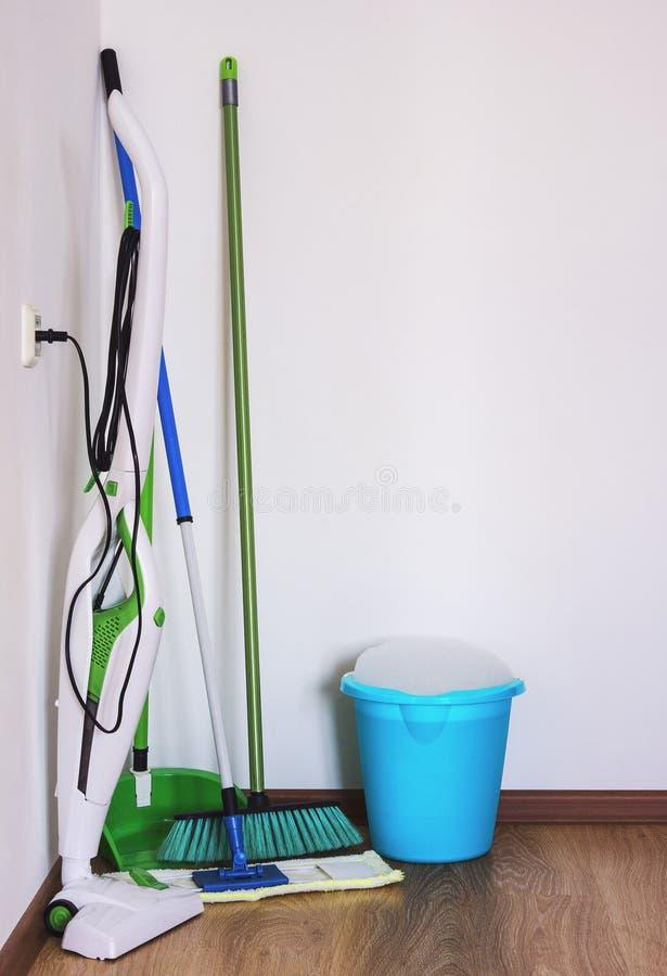 Um aspirador de p30, um espanador e uma vassoura imagem de stock