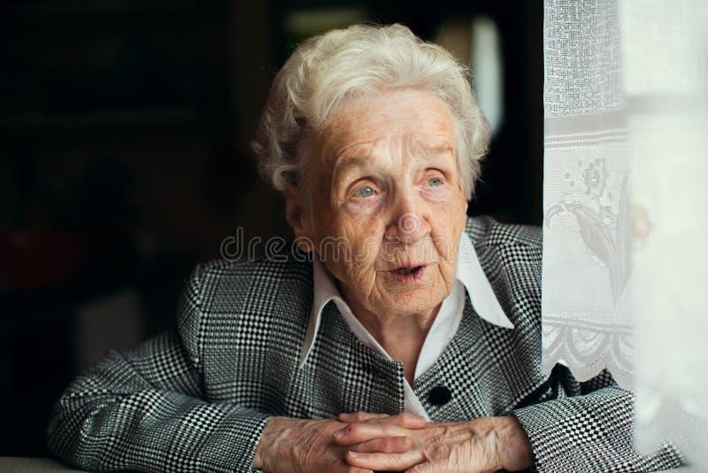 Um assento de pensamento da mulher idosa pela janela pensioner imagem de stock royalty free