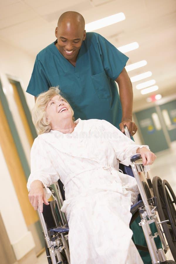 Um assistente hospitalar que empurra uma mulher sênior em uma cadeira de rodas imagens de stock royalty free