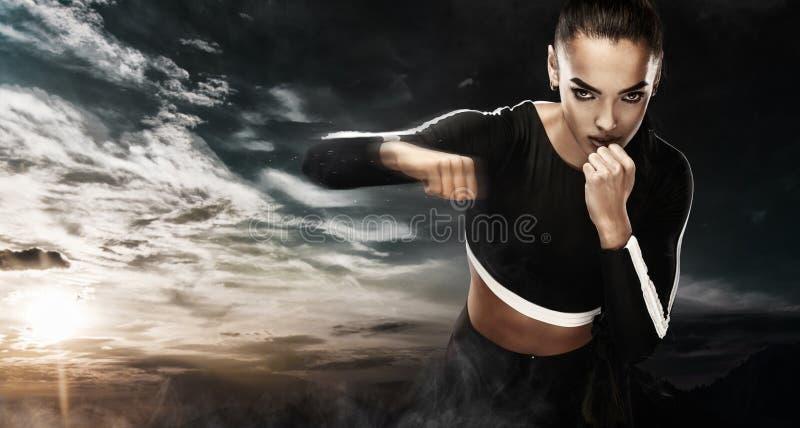 Um atlético forte, pugilista da mulher, encaixotando no treinamento no fundo do céu Conceito do encaixotamento do esporte com esp imagens de stock royalty free