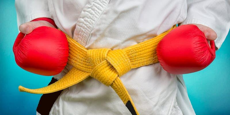 Um atleta do karaté em um quimono com uma correia amarela e as luvas imagens de stock
