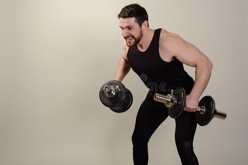Um atleta novo executa um exercício com os pesos no desenvolvimento dos músculos dos ombros foto de stock
