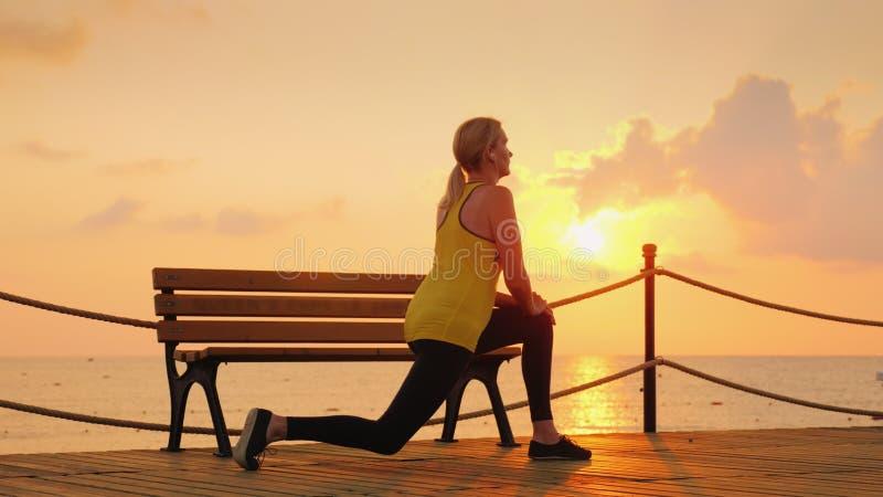 Um atleta novo faz um aquecimento da manhã no cais do mar de uma manhã fresca na perspectiva do sol de aumentação fotografia de stock