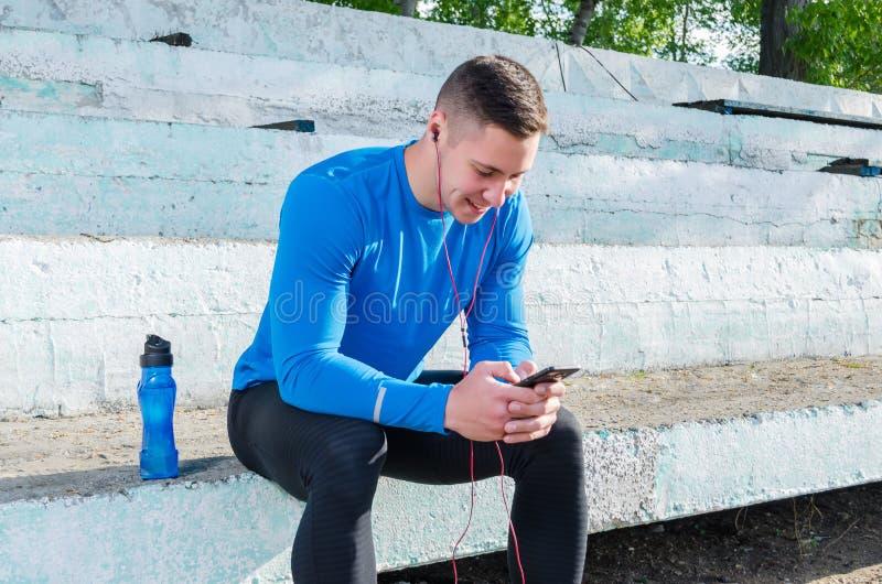 Um atleta novo senta-se nos suportes e escuta-se a música após a formação fotos de stock