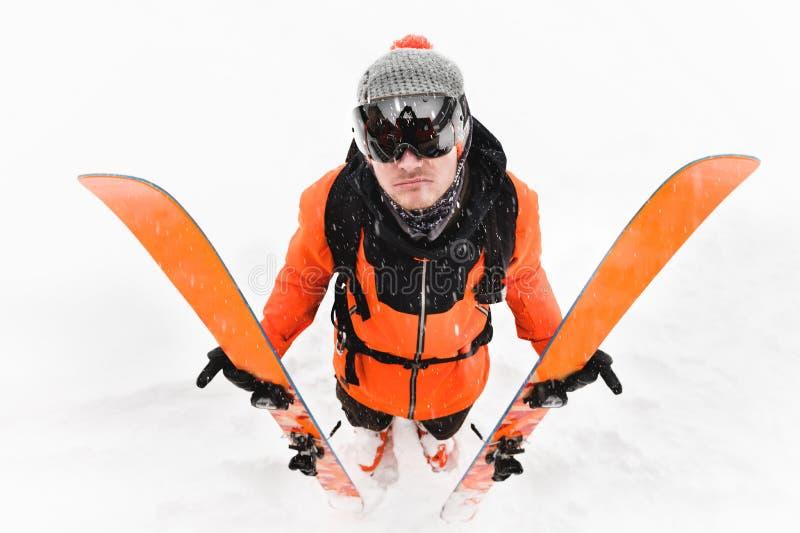 Um atleta profissional do esquiador em um terno preto alaranjado com uma máscara de esqui preta com os esquis em seus suportes da imagens de stock royalty free