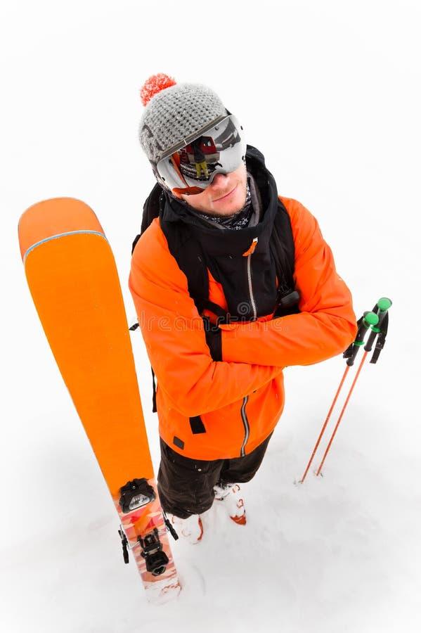 Um atleta profissional do esquiador no terno preto alaranjado com uma máscara de esqui preta com os esquis ao lado dela com mãos  fotografia de stock royalty free