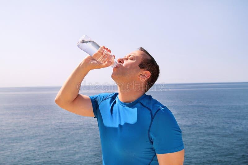 Um atleta que faz uma ruptura durante o treinamento, agua potável fresca bebendo de uma garrafa, descansa e aprecia o ar puro foto de stock royalty free