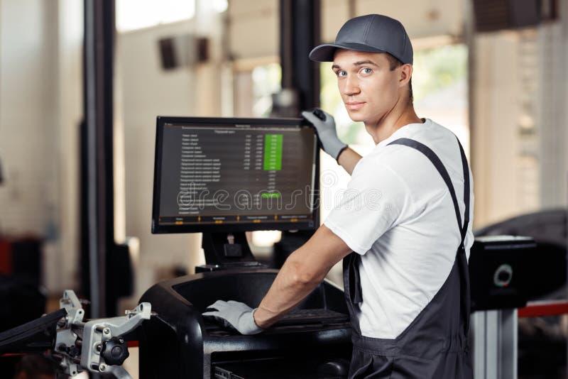 Um automechanic bonito no uniforme está conduzindo um diagnóstico do automóvel imagem de stock royalty free