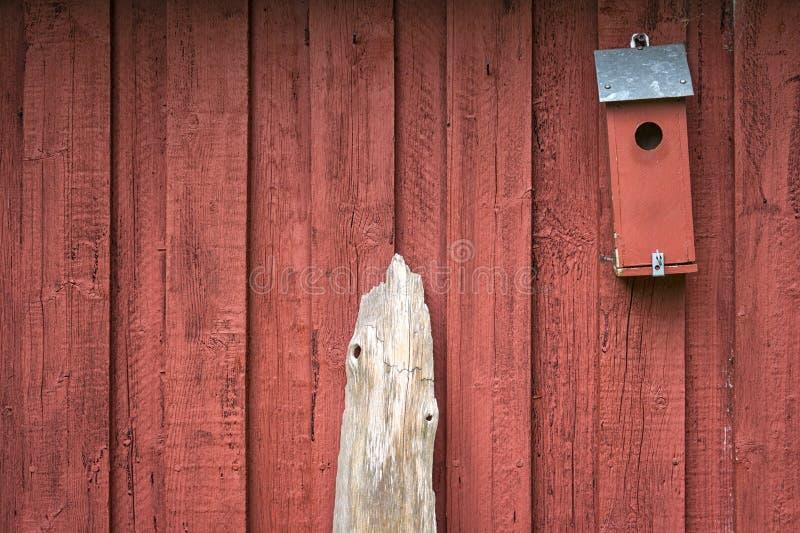 Um aviário e uma madeira lançada à costa pequenos na frente de uma construção escandinava typival foto de stock royalty free