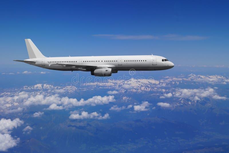 Um avião comercial em voo sobre a cordilheira a mais alta em Europa Montanhas dos alpes imagem de stock royalty free