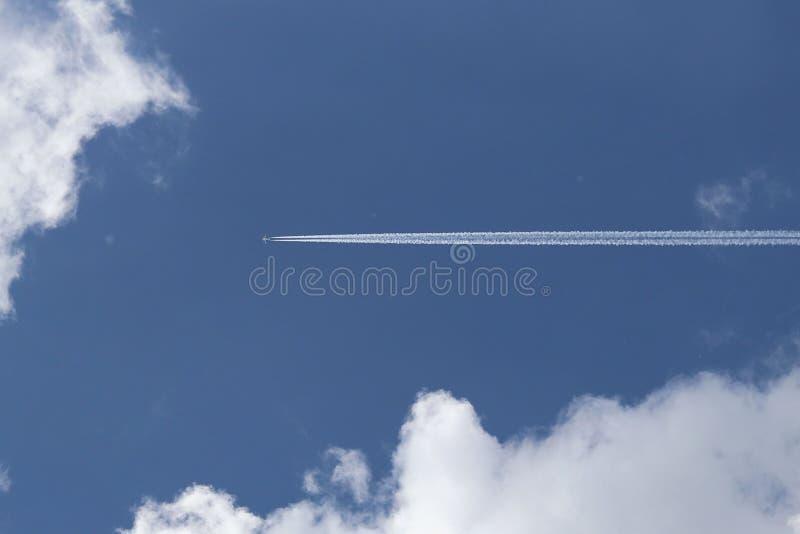 Um avião do passageiro que voa altamente no céu entre as nuvens Forro de ar que deixa um traço de gáss de exaustão que incandesce fotografia de stock