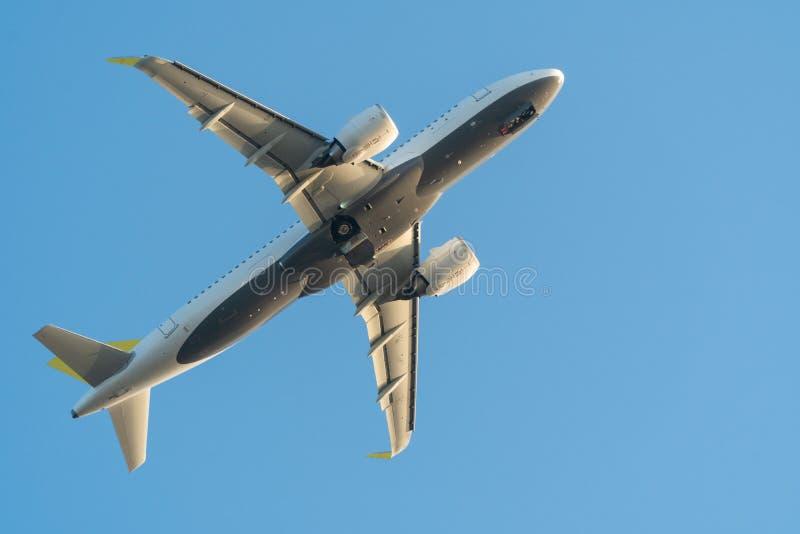 Um avião ou um plano estão voando sobre o céu azul O trem de aterrissagem é em processo da armazenagem Lugar para o texto imagens de stock