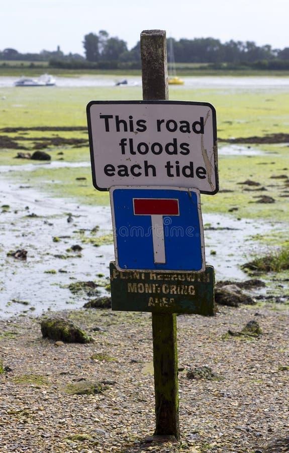 Um aviso do sinal contra o estacionamento do carro em uma estrada que inunde com cada maré alta imagem de stock