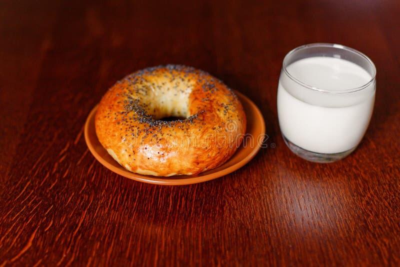 Um bagel e um leite deliciosos em uma tabela de madeira imagens de stock royalty free