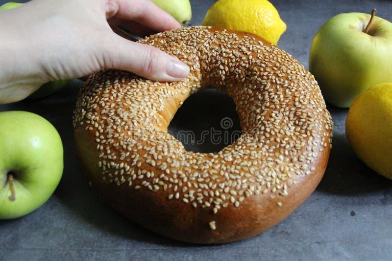 Um bagel fresco com sementes de s?samo A m?o f?mea quebra um bagel foto de stock