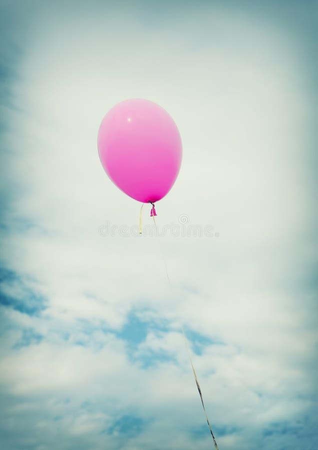 Um balão cor-de-rosa com corda em um céu azul foto de stock
