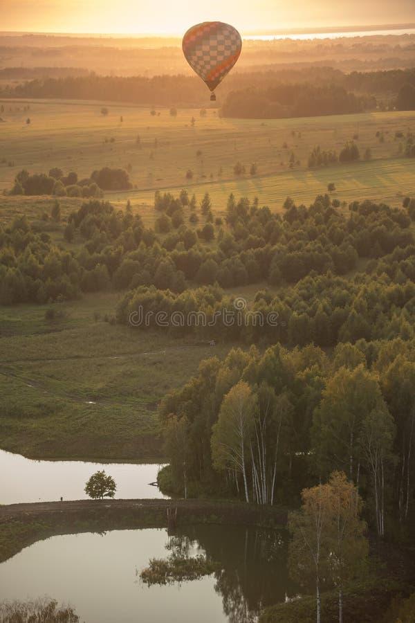Um balão de ar que voa sobre o campo e os reservatórios usando a tecnologia do calor - por do sol brilhante fotos de stock