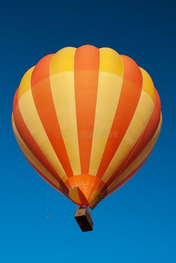 Um balão de ar quente colorido e um céu azul claro fotos de stock royalty free