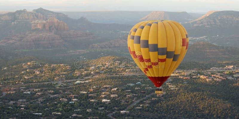 Um balão de ar quente sobe acima de Sedona, o Arizona fotos de stock royalty free