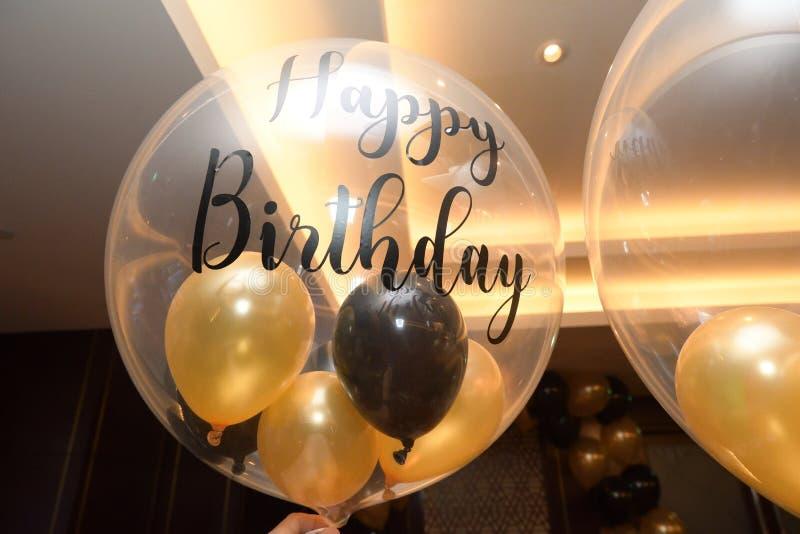 Um balão transparente com balões amarelos e negros menores dentro e as palavras Parabéns impressos nele imagens de stock royalty free