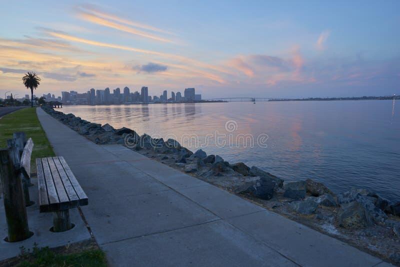Um banco dá boas-vindas a qualquer um que deseja olhar os nasceres do sol gloriosos sobre a baía de Coronado, San Diego, Califórn imagens de stock royalty free