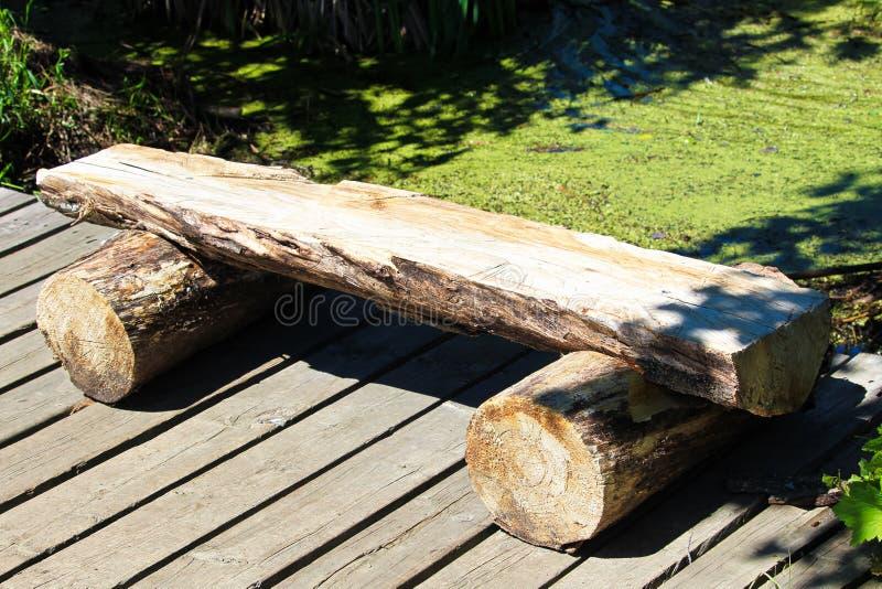 Um banco de madeira do log da separação em uma fuga do passeio à beira mar imagem de stock royalty free