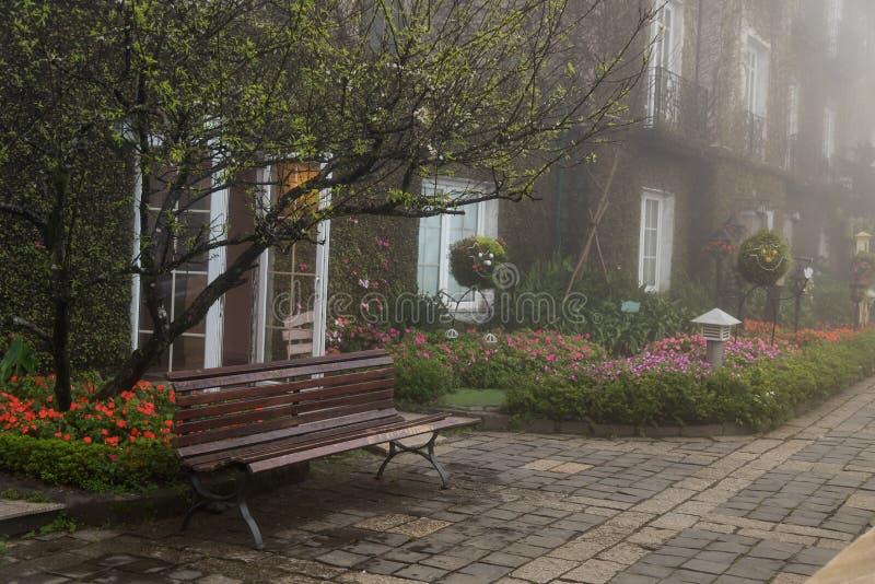 Um banco de madeira vazio no jardim de flores fotografia de stock royalty free