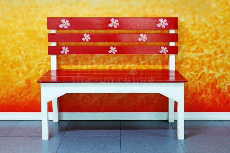Um banco de madeira vermelho bonito no parque da cidade foto de stock royalty free