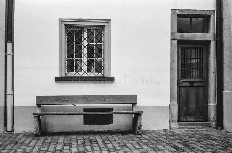 Um banco em frente a uma casa medieval no centro de Chur na Suíça fotografou com técnica analógica em preto e branco imagem de stock
