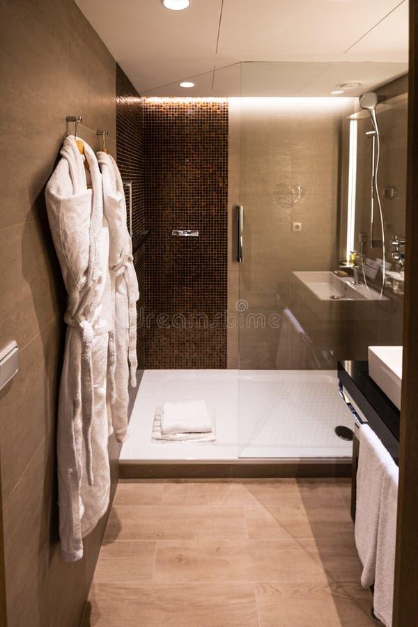 Um banheiro recentemente renovado em um hotel fino com uma caminhada no chuveiro e as vestes em uma sala brilhantemente iluminada fotos de stock