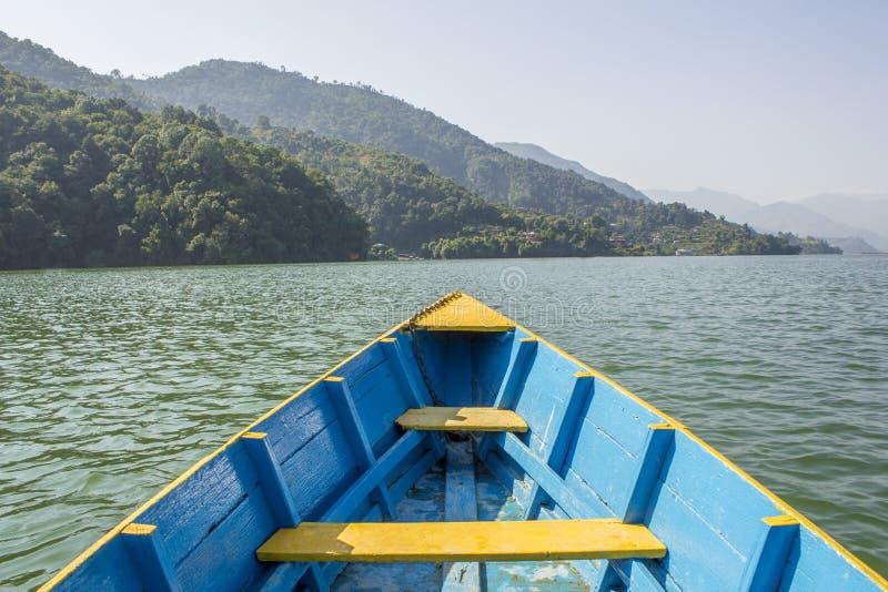 Um barco amarelo azul de madeira no lago na perspectiva das montanhas verdes foto de stock