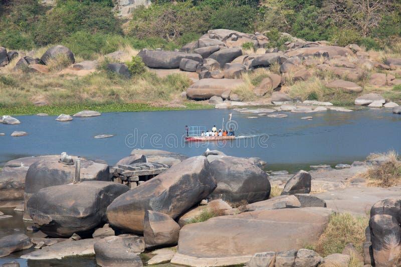 Um barco com os povos que navegam ao longo do rio fotos de stock