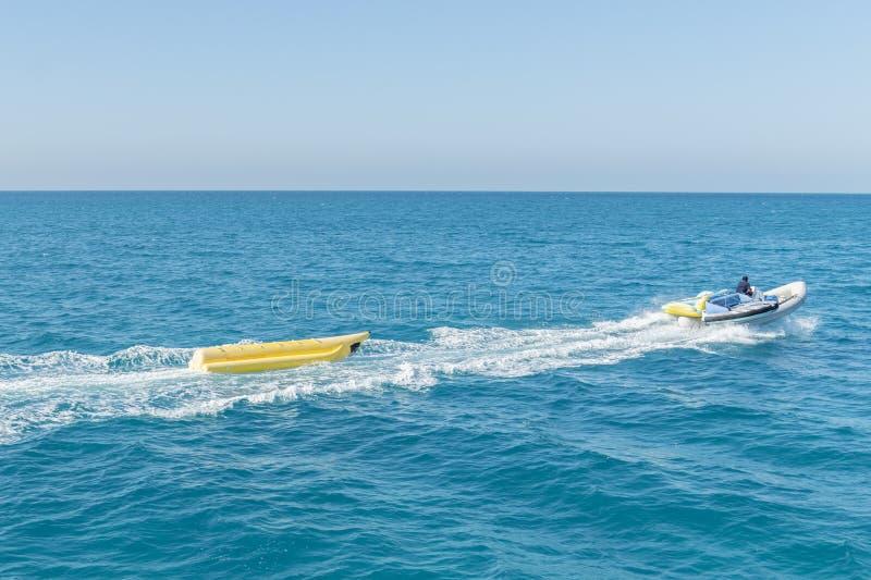Um barco de banana que flutua no mar perto da praia fotografia de stock