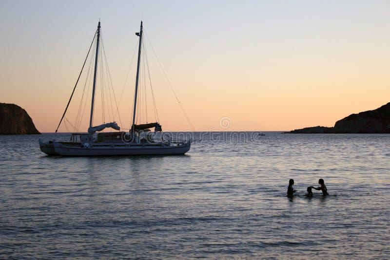 Um barco de navigação na baía no por do sol, ilha de Vathi de Sifnos, Grécia imagem de stock royalty free