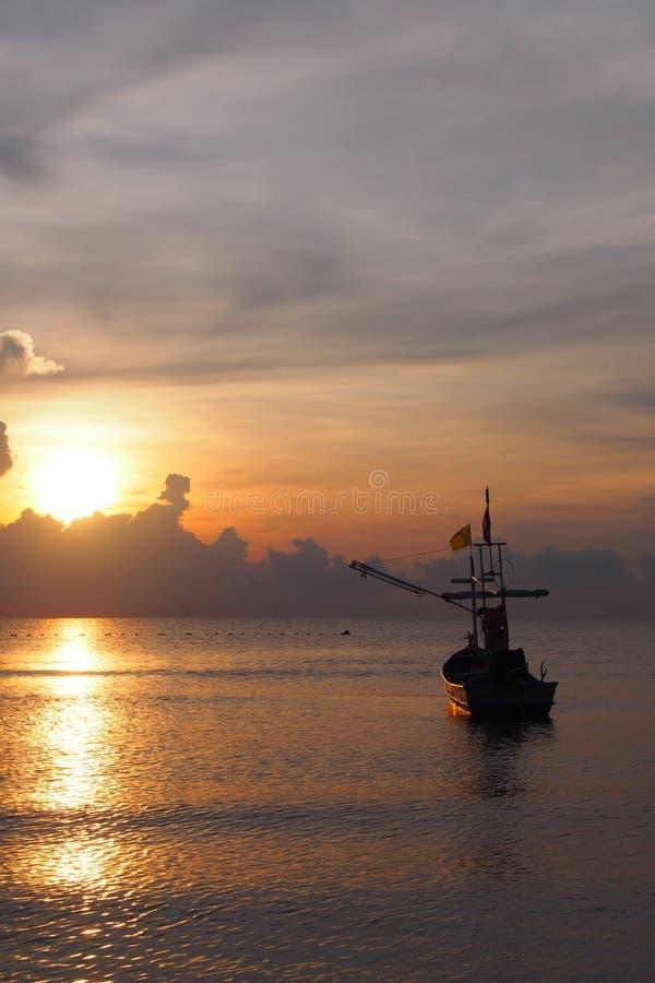 Um barco de pesca com nascer do sol, as cores do céu da manhã foto de stock