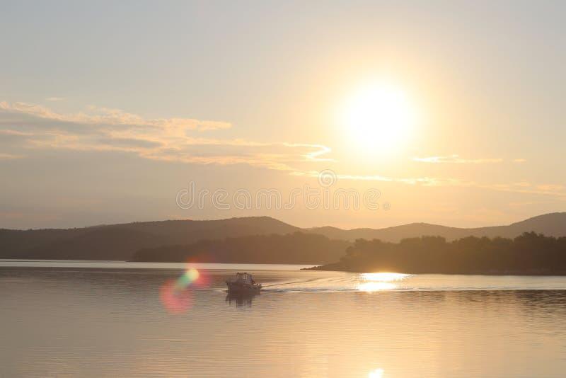 Um barco de pesca cruza a baía do mar no sol da manhã Alvorecer no recurso Trabalho pesado do ser humano Calma e resto após o cru fotos de stock royalty free