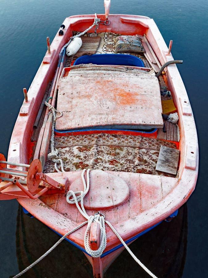 Um barco de pesca grego tradicional velho amarrado acima no porto da vila fotos de stock