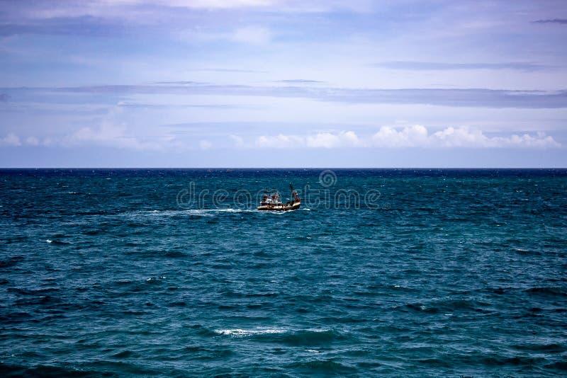 Um barco de pesca que dirige para fora ao mar fotografia de stock