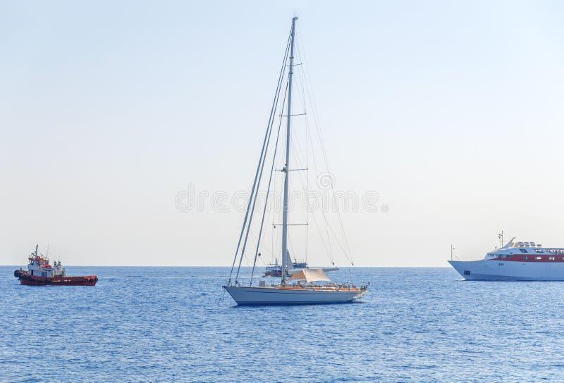 Um barco extravagante entrou no mar e no barco três que passam perto com céu limpo imagem de stock