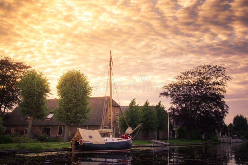 Um barco holandês tradicional da navigação ancorado em um canal fora de uma casa com o céu nebuloso dourado, Holanda imagem de stock royalty free