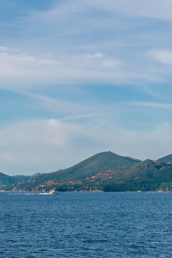 Um barco no mar com as montanhas de Toscânia no fundo imagens de stock royalty free