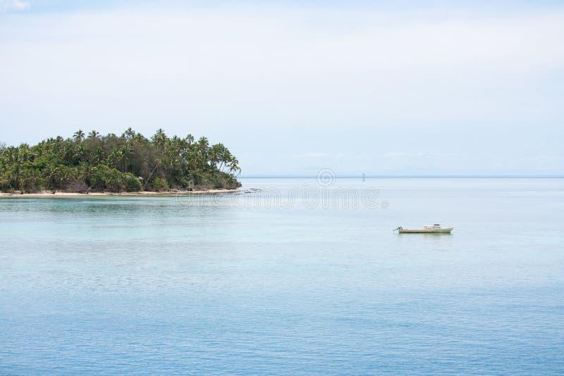 Um barco pequeno e uma ilha tropical em Tonga foto de stock