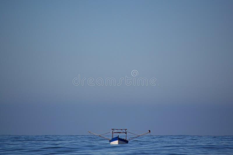 Um barco pequeno funciona com shrimpnet imagens de stock royalty free