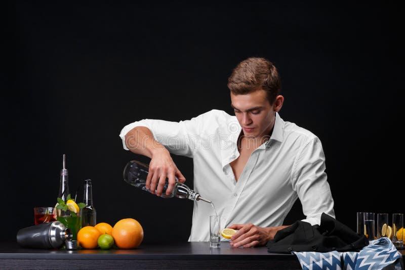 Um barman bonito derrama uma bebida em um vidro, um contador da barra com fatias do cal, limão em um fundo do preto escuro imagem de stock
