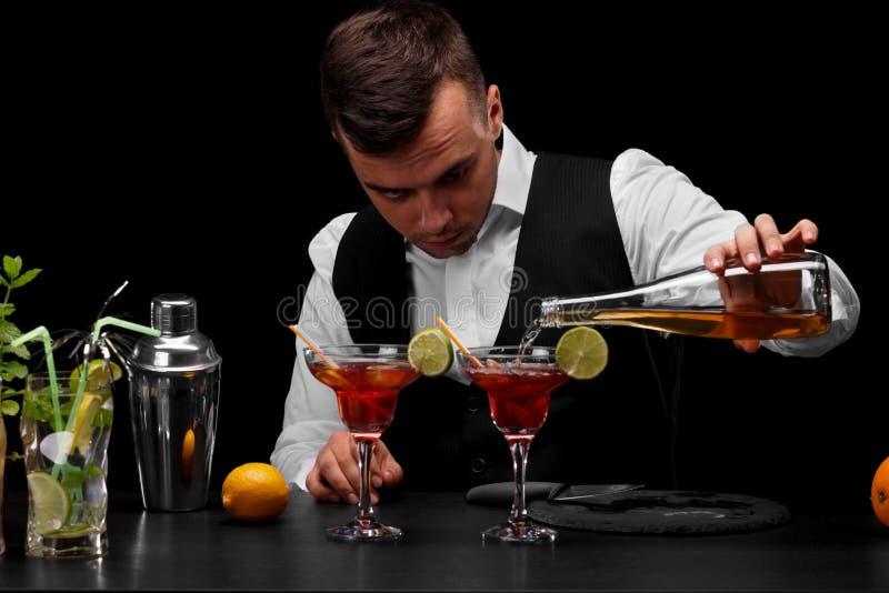Um barman encantador derrama um cocktail nos vidros do margarita, fatias de cal, limão, fatias de cal em um fundo preto imagem de stock royalty free