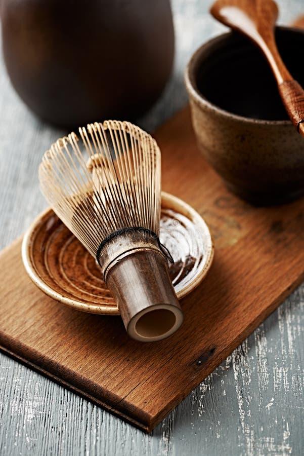 Um batedor de ovos de bambu para o chá do matcha em uma placa cerâmica fotografia de stock royalty free