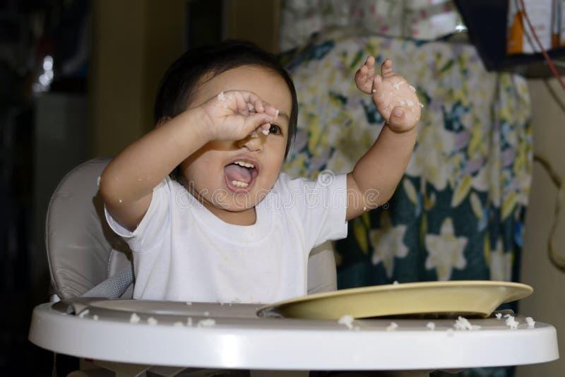 Um bebê asiático do bebê de um ano que aprende comer só pela colher, desarrumado no bebê que janta a cadeira fotografia de stock