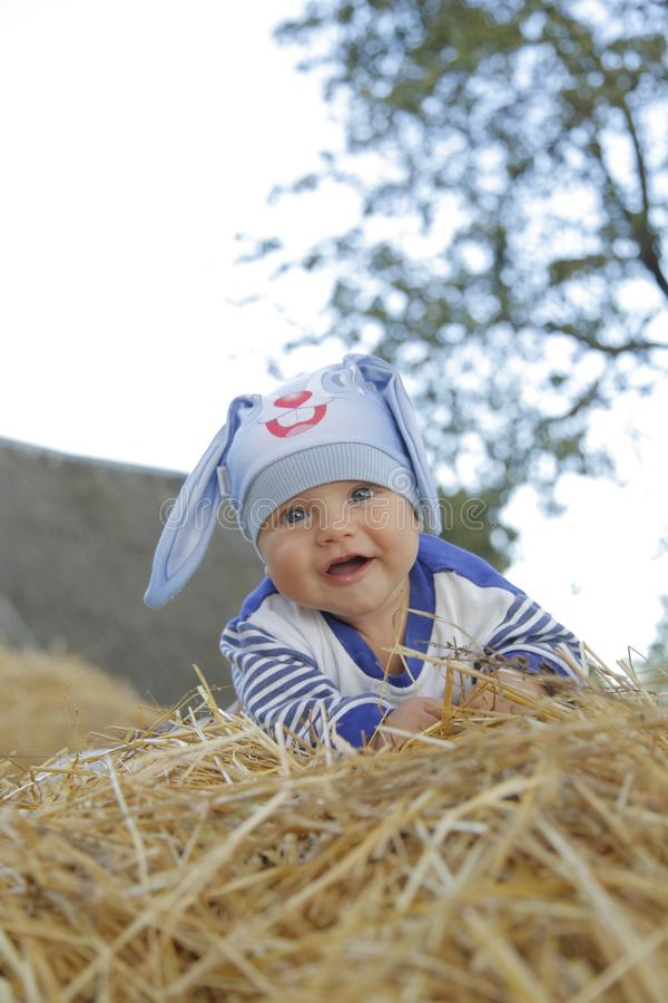 Um bebê bonito em um terno do coelho encontra-se na palha imagens de stock royalty free