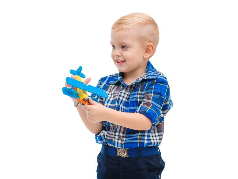 Um bebê bonito fascinantemente que joga com um avião do brinquedo e que olha afastado Isolado no branco foto de stock royalty free