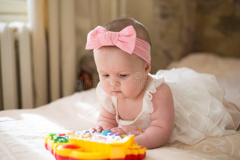 Um bebê brincando com brinquedo em casa menina feliz deitada na cama no berçário fotografia de stock